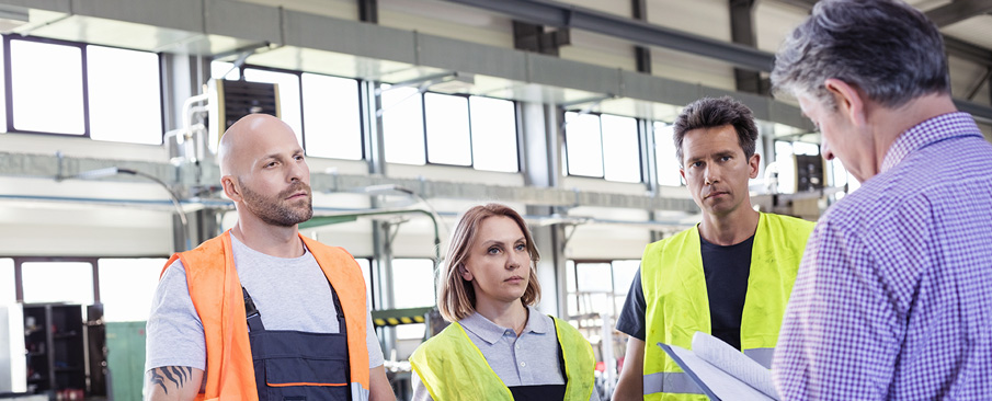 Career Training: 3 people wearing protective vests listening to a man with back to camera.